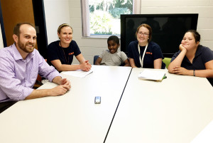 Dr. David Fedele and graduate students Marie Chardon and Casey Lawless  meet with Gerquon (third from left) and Elizabeth (far right), participants in Fedele's pediatric asthma management study. Study meetings are held at HealthStreet's community center.
